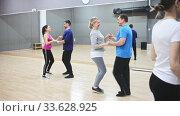 Купить «Mature dancing couple enjoying social dance during group class in modern studio», видеоролик № 33628925, снято 31 мая 2020 г. (c) Яков Филимонов / Фотобанк Лори