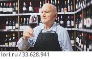 Confident elderly male winemaker holding glass of red wine, checking it in wine store. Стоковое видео, видеограф Яков Филимонов / Фотобанк Лори