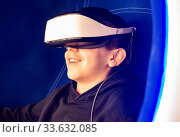 Купить «Child playing game with VR glasses. Blue illuminated cabin with joysticks. Special effects. Technology, entertainment and gaming concept with virtual reality glasses.», фото № 33632085, снято 8 июля 2020 г. (c) easy Fotostock / Фотобанк Лори