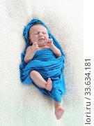Маленький новорожденный ребенок в синей пеленке скорчился от боли. Стоковое фото, фотограф Наталья Гармашева / Фотобанк Лори