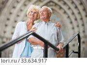 Loving mature spouses standing near ancient cathedral. Стоковое фото, фотограф Яков Филимонов / Фотобанк Лори