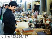 Portrait of senior woman choosing vintage goods at flea market. Стоковое фото, фотограф Яков Филимонов / Фотобанк Лори