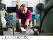 Купить «Concentrated worker is shaping timber on woodworking machine at the factory», фото № 33636253, снято 5 августа 2020 г. (c) Яков Филимонов / Фотобанк Лори