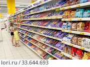 Купить «Children choose sweets in confectionery department of supermarket. Girls choose bar of chocolate in shop. Little sisters in shop of different sweets. girl choosing tasty candies in candy shop.», фото № 33644693, снято 19 июня 2019 г. (c) easy Fotostock / Фотобанк Лори