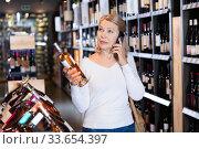 Купить «Modern stylish mature woman talking on phone advising with someone about purchasing of wine in winehouse», фото № 33654397, снято 27 мая 2020 г. (c) Яков Филимонов / Фотобанк Лори