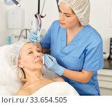 Senior woman getting injection for facial rejuvenation procedure in esthetic clinic. Стоковое фото, фотограф Яков Филимонов / Фотобанк Лори