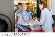 Купить «Female client receiving her clean clothes at dry-cleaning salon», фото № 33654617, снято 22 января 2019 г. (c) Яков Филимонов / Фотобанк Лори