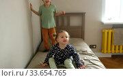 Купить «Siblings jumping on bed at home», видеоролик № 33654765, снято 21 апреля 2020 г. (c) Ekaterina Demidova / Фотобанк Лори