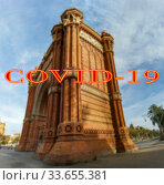 Coronavirus in Barcelona, Spain. Covid-19 sign on a blurred background. Concept of COVID pandemic and travel in Europe. Arc de Triomf. Стоковое фото, фотограф Владимир Журавлев / Фотобанк Лори