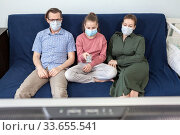 A bored Caucasian family wearing medical masks sitting on sofa at home watching television, teenager girl with tv remote control. Стоковое фото, фотограф Кекяляйнен Андрей / Фотобанк Лори
