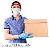 Купить «Courier with cardboard box from delivery service, man with medical mask and blue neoprene gloves, isolated on white background», фото № 33655565, снято 23 апреля 2020 г. (c) Кекяляйнен Андрей / Фотобанк Лори