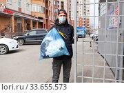 Man taking out garbage during coronavirus pandemic, it is allowed without any permission. Стоковое фото, фотограф Кекяляйнен Андрей / Фотобанк Лори