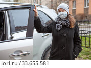 Caucasian woman wearing black coat and one-use face mask standing next to her car with opened door. Стоковое фото, фотограф Кекяляйнен Андрей / Фотобанк Лори