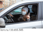Portrait of Caucasian adult woman a driver sitting in car wearing facial mask to prevent coronavirus infection. Стоковое фото, фотограф Кекяляйнен Андрей / Фотобанк Лори