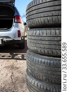 Купить «Close up view of summer tyre with open trunk of passenger car, seasonal wheel change», фото № 33655589, снято 22 апреля 2020 г. (c) Кекяляйнен Андрей / Фотобанк Лори