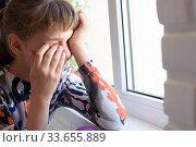 Обиженная девочка горько плачет у окна. Стоковое фото, фотограф Иванов Алексей / Фотобанк Лори
