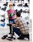 Man seller assisting boy in trying on roller-skates. Стоковое фото, фотограф Яков Филимонов / Фотобанк Лори