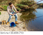 Adult man standing near river and pulling fish expressing emotions of dedication. Стоковое фото, фотограф Яков Филимонов / Фотобанк Лори