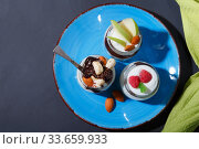 Купить «Sweet tasty milk curd creamy food in a glass jar of homemade breakfast. Cheesecake, English Trifle, Eton dessert, tiramisu, zuppa Inglese with nuts, almonds, cashews, hazelnuts, candied fruits and chocolate sauce», фото № 33659933, снято 14 декабря 2019 г. (c) Светлана Евграфова / Фотобанк Лори