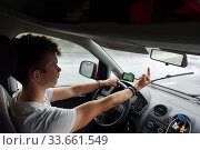 Berlin, Germany, young man shows his middle finger while driving (2018 год). Редакционное фото, агентство Caro Photoagency / Фотобанк Лори