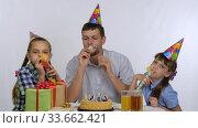 Девочки и отец радостно дуют в дудки свистелки на празднике дня рождения. Стоковое видео, видеограф Иванов Алексей / Фотобанк Лори