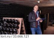 Winemaker with clipboard in winery vault. Стоковое фото, фотограф Яков Филимонов / Фотобанк Лори