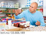Focused man choosing fresh products during shopping at food store. Стоковое фото, фотограф Яков Филимонов / Фотобанк Лори