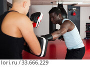 Men practicing effective techniques of self-defence during individual class in training room. Стоковое фото, фотограф Яков Филимонов / Фотобанк Лори