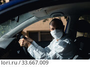 Caucasian man sitting in a car wearing a coronavirus covid19 mask. Стоковое фото, агентство Wavebreak Media / Фотобанк Лори