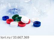 Купить «Colorful plastic caps against bottles. Plastic wrapping rubbish on blue background. Concept of environmental pollution», фото № 33667369, снято 30 апреля 2020 г. (c) Papoyan Irina / Фотобанк Лори