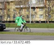 """Купить «Курьер сервиса быстрой доставки еды """"Delivery Club"""" едет на велосипеде по Хабаровской улице в дни самоизоляции при коронавирусе COVID-19. Район Гольяново. Город Москва», эксклюзивное фото № 33672485, снято 26 апреля 2020 г. (c) lana1501 / Фотобанк Лори"""