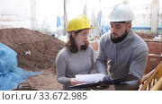 Купить «Two confident engineers discussing blueprint while standing at construction site», видеоролик № 33672985, снято 11 декабря 2019 г. (c) Яков Филимонов / Фотобанк Лори