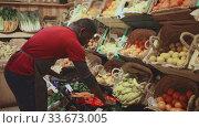 Focused African man working at farmer market, putting fresh fruits and vegetables on showcase. Стоковое видео, видеограф Яков Филимонов / Фотобанк Лори
