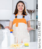 Купить «Young woman in uniform standing before cleaning in office», фото № 33679457, снято 18 апреля 2018 г. (c) Яков Филимонов / Фотобанк Лори