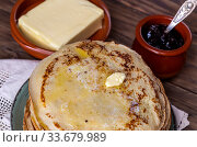 A many of fresh, hot pancakes with butter on a plate and jam in a bowl close-up. Стоковое фото, фотограф Татьяна Ляпи / Фотобанк Лори