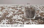 Купить «Fresh aromatic coffe beans are falling in a glass cup and table.», видеоролик № 33681493, снято 31 августа 2018 г. (c) Ярослав Данильченко / Фотобанк Лори