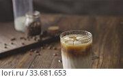 Купить «Freshly prepared ice coffee drink and fragrant beans on a wooden table.», видеоролик № 33681653, снято 18 марта 2019 г. (c) Ярослав Данильченко / Фотобанк Лори