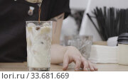 Купить «Barista girl pours hot coffee into a glass with milk and ice, drops drip onto a wooden table. Full HD video, 240fps, 1080p.», видеоролик № 33681669, снято 14 марта 2019 г. (c) Ярослав Данильченко / Фотобанк Лори