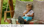 A funny four-year-old boy enjoys eating raspberries on a village swing. Стоковое видео, видеограф Aleksandr Lutcenko / Фотобанк Лори