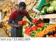 Купить «Seller arranging vegetables and fruits on counter», фото № 33682069, снято 13 февраля 2020 г. (c) Яков Филимонов / Фотобанк Лори