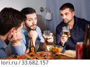 Купить «Troubled male friends talking, drinking beer with pizza at home», фото № 33682157, снято 10 января 2018 г. (c) Яков Филимонов / Фотобанк Лори