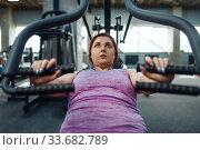Купить «Overweight woman on exercise machine, top view», фото № 33682789, снято 28 декабря 2019 г. (c) Tryapitsyn Sergiy / Фотобанк Лори