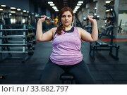 Купить «Overweight woman poses with dumbbells in gym», фото № 33682797, снято 28 декабря 2019 г. (c) Tryapitsyn Sergiy / Фотобанк Лори