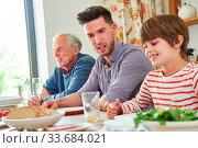 Erweiterte Familie mit Opa und Enkel beim Mittagessen oder Abendessen. Стоковое фото, фотограф Zoonar.com/Robert Kneschke / age Fotostock / Фотобанк Лори