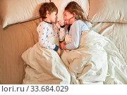 Bruder und Schwester liegen im Bett im Schlafzimmer und albern fröhlich herum. Стоковое фото, фотограф Zoonar.com/Robert Kneschke / age Fotostock / Фотобанк Лори