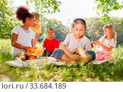 Купить «Multikulturelle Kinder beim Picknick auf einer Wiese im Sommer», фото № 33684189, снято 25 мая 2020 г. (c) age Fotostock / Фотобанк Лори