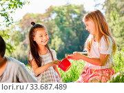 Купить «Zwei Mädchen teilen sich ihr Essen beim Picknick auf einer Sommer Wiese», фото № 33687489, снято 25 мая 2020 г. (c) age Fotostock / Фотобанк Лори