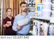 Купить «couple is choosing paint with shop list», фото № 33697845, снято 16 февраля 2018 г. (c) Яков Филимонов / Фотобанк Лори