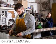 Купить «Engineer measures metal sheet with a tape measure», фото № 33697993, снято 27 мая 2020 г. (c) Яков Филимонов / Фотобанк Лори