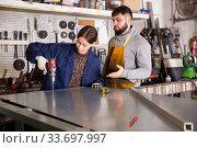 Foreman controlling workwoman drilling metal structures. Стоковое фото, фотограф Яков Филимонов / Фотобанк Лори